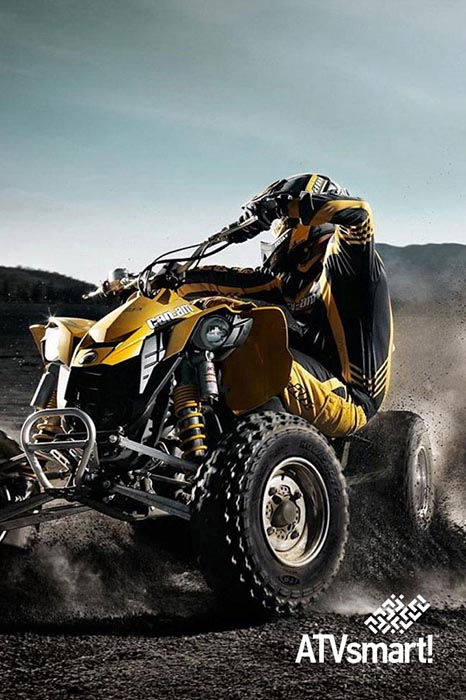 Man on yellow ATV riding through dirt tracks