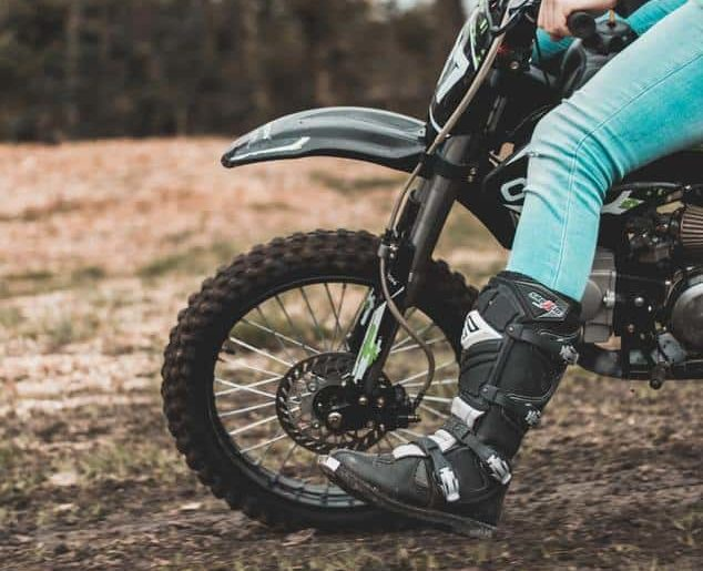 Dirt bike front tire with riders leg in front for balance.