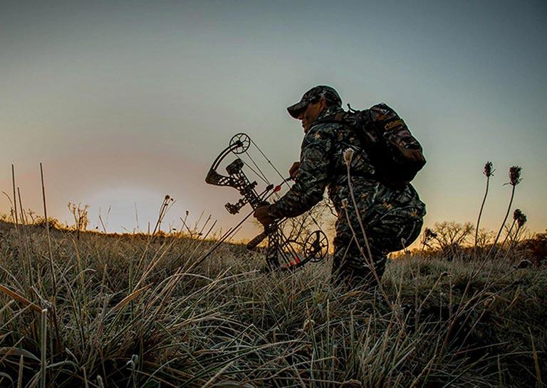 Chasseur avec un arc dans les hautes herbes au crépuscule