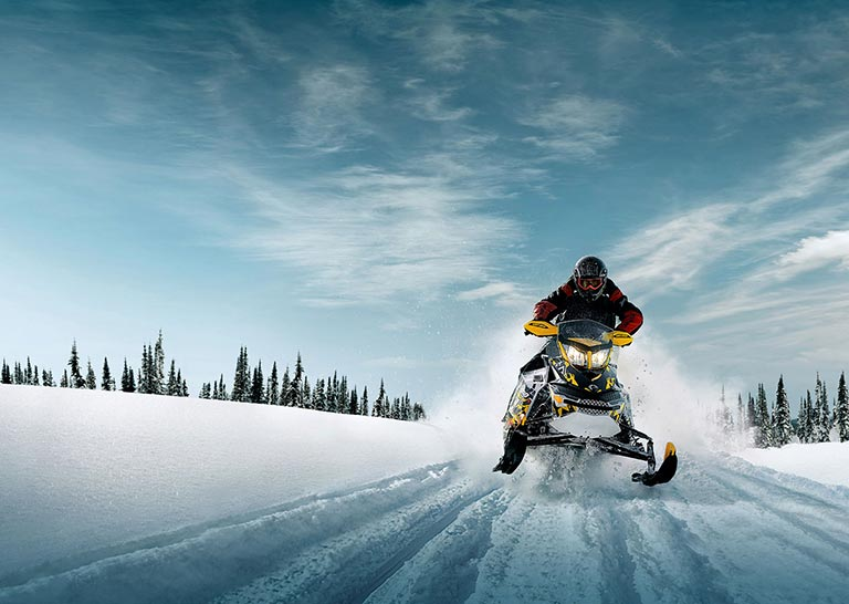Person on snowmobile riding through snowy trail