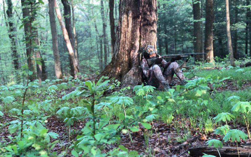 Campfire Collective Hunting Ambassador Danielle Lynise sitting against a tree aiming her shotgun on a hunt.