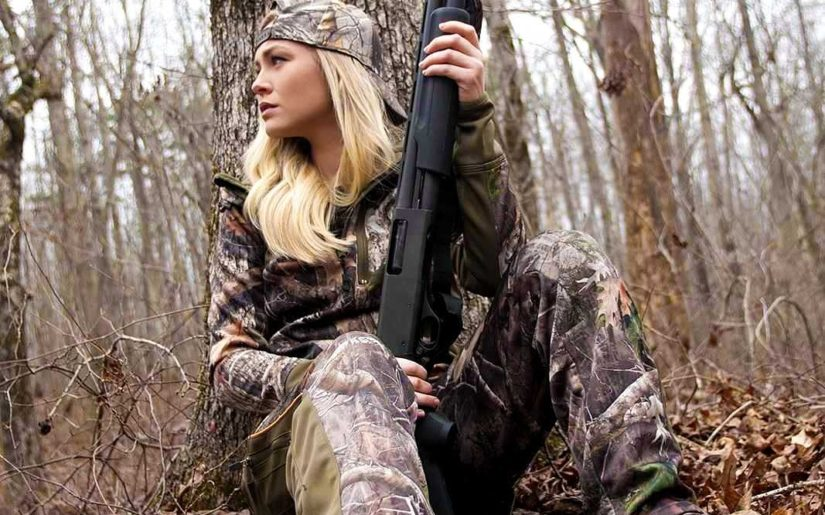Campfire Collective Hunting Ambassador Ashley Dill wearing camouflage, holding a shotgun, leaning against a tree.