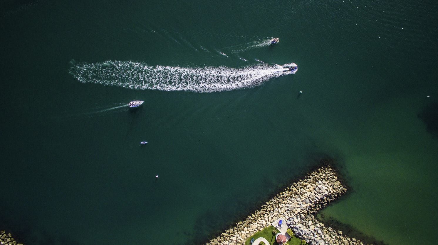 Aerial view of powerboats and personal  watercraft (PWC) on aqua-colored water.