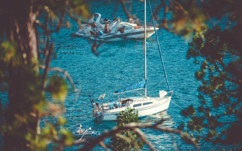Sailboat and powerboats anchored on a sandbar.