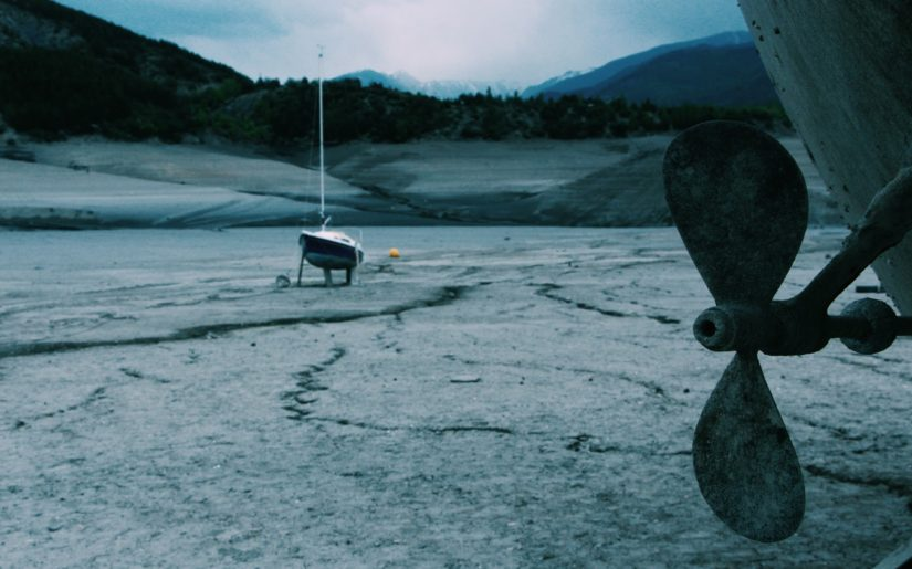 Sailboats sitting on blocks in a dried-up riverbed.
