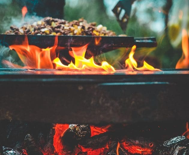 Cooking on a skillet over a campfire.
