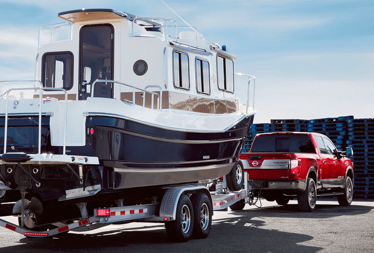 Red Nissan Titan towing massive boat, parking on a pier.