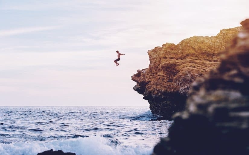 Swimmer jumping into ocean from cliffs.