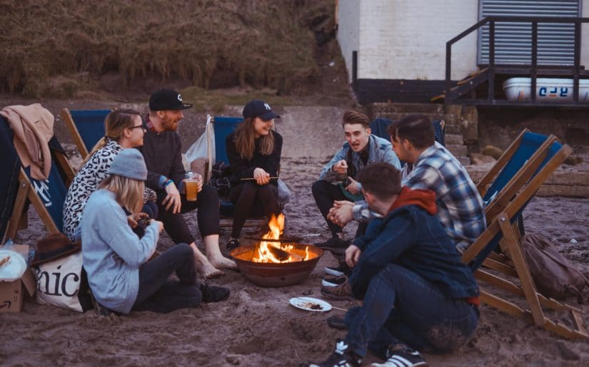 Group of young adults sitting around campfire on beach.