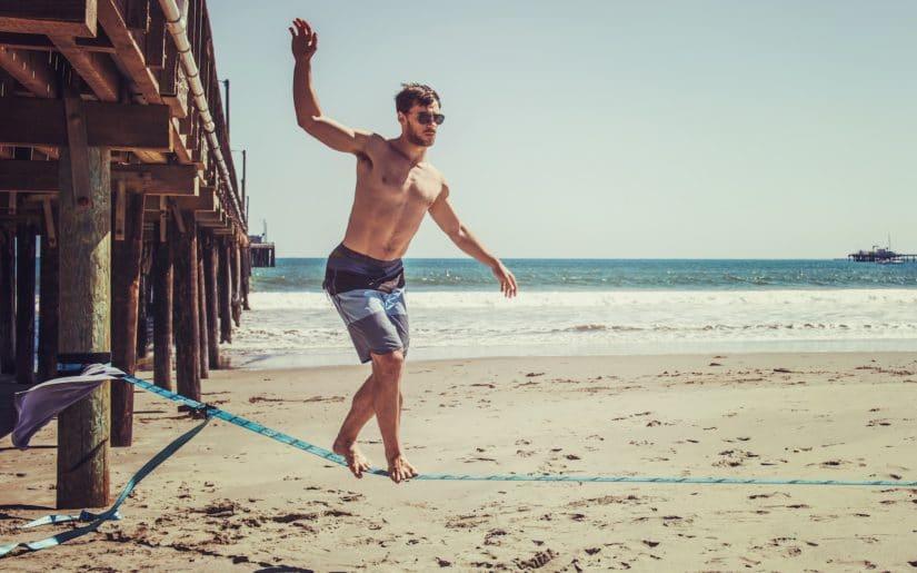 Man balancing on a slackline on beach beside a pier.