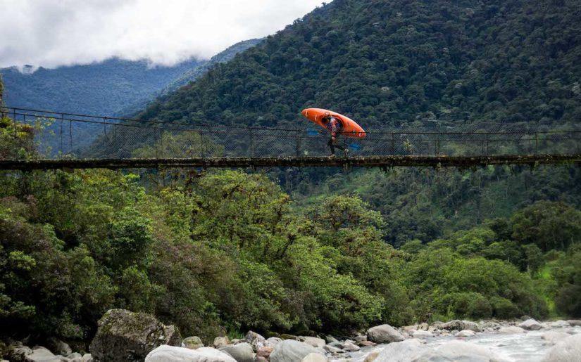 Man carrying kayak on suspended bridge, over an Ecuador river.